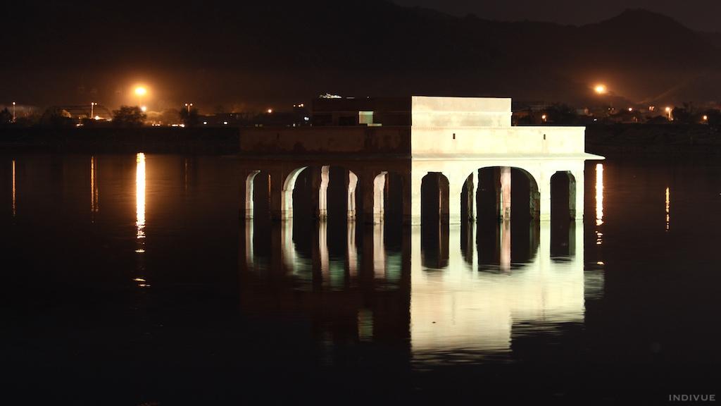 Osa Jal Mahalin rakennusta ja heijastus veteen iltapimeässä Jaipurissa, Intiassa