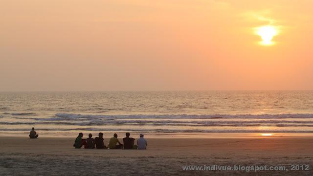 Turisteja Goan rannalla katsomassa vuoden viimeistä auringonlaskua