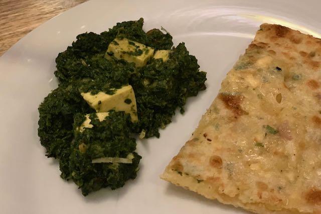 Intialainen ruoka-annos Palak Paneer ja valkosipulinaanleipä Namaste India -ravintolassa